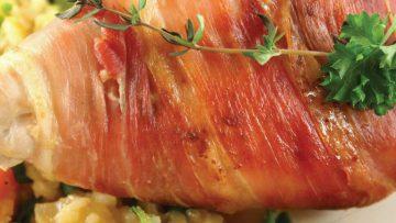 Kipfilet, gevuld met pesto, geitenkaas en tomaten ingerold met Parmaham uit de oven