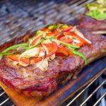 Gegrilde Ribeye steak met pepers en uien op cederhout